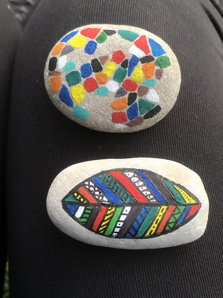 Photo of stones painted in bright colours, one with added detail lines